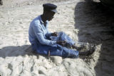 Senegal, fisherman repairing nets
