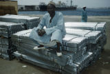 Dakar, man seated on imported goods at port