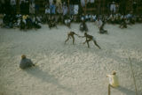 Senegal, spectators watching men wrestling in sand