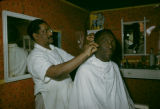 Senegal, man getting haircut from barber