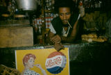 Africa, man in shop with pepsi ad