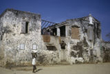Senegal, child carrying basin on head in front of old building