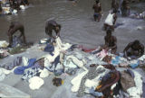 Côte d'Ivoire, men washing fabric in river