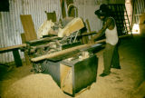 Nigeria, worker sawing lumber at sawmill in Lagos