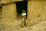 Nigeria, Fula girl outside mud-walled home