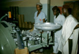 Nigeria, men observing machinery at Nicco Sweets Factory in Kano