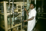 Nigeria, worker operating food processing machinery
