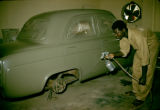 Africa, worker spray painting automobile