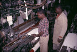 Nigeria, workers operating loom at textile factory