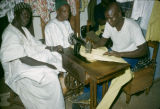 Africa, men watching tailor sew clothing