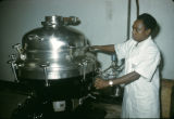 Nigeria, worker operating machinery at factory