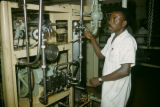 Nigeria, man operating food processing machinery