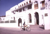 Tanzania, boy bicycling past former Sultan's Palace in Zanzibar