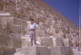 Egypt, tourist standing on stones of pyramid in Giza
