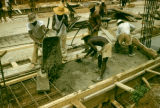Tanzania, workers pouring cement at construction site in Dar es Salaam