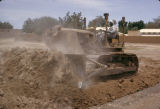 Sudan, man operating tractor at construction site