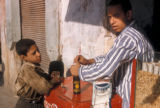 Cairo (Egypt), boy buying a soft drink from a street vendor