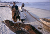 Nigeria, men working with fishing nets on beach