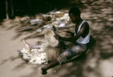 Zambia, man carving wood mask in village