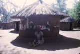 Zambia, woman sitting in front of painted hut in village