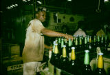 Nigeria, worker operating machinery at brewery in Lagos