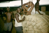 Nigeria, laborers posing on bales of rope