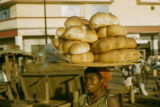 Nigeria, woman carrying bread for sale at market