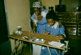 Democratic Republic of the Congo, woman teaching another woman how to weave textiles