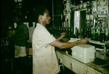 Nigeria, worker operating machinery at brewery