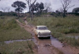 Uganda, car passing through flooded dirt road