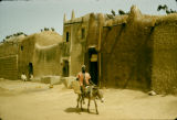 Nigeria, man riding donkey past adobe buildings in Kano
