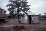 Uganda, man standing outside prefabricated hut in kraal