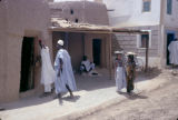 Nigeria, people outside adobe houses