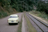 Democratic Republic of the Congo, car parked on highway along railroad tracks