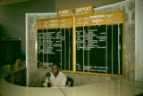 Nigeria, man at desk in front of timetable at Kano Airport
