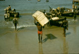 Ghana, men unloading cargo from boats on coast of Accra