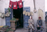 Tunisia, men sitting outside produce shop adorned with Tunisian flags