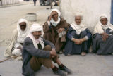 Tunisia, men resting on ground outside building