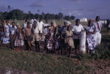 Kenya, group of adults and children gathered in field in Mombasa