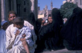 Cairo (Egypt), street scene with veiled women and a man carrying a child