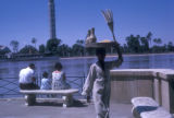 Cairo (Egypt),  the Nile waterfront with a street vendor carrying snacks on his head