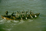 Ghana, men rowing boat with cargo from ship in Gulf of Guinea off Accra coast