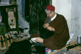 Tunisia, man working with fabric in tailor shop