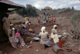 Kenya, Kikuyu women resting outside mud-walled home