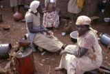 Kenya, Kikuyu women sitting outside mud-walled home