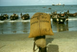 Ghana, man carrying bag of cocoa to boats on Accra coast