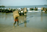 Ghana, men carrying bags of cocoa to boats on Accra coast
