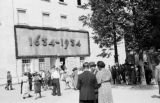 Germany, people gathered outside building with '1634-1934' sign in Oberammergau