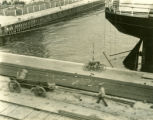 Poland, man pulling empty wagon next to stern of steamer Kosciuscko