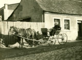 Poland, carriage resting in side street in front of house